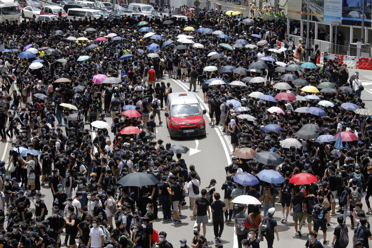 Image: A taxi makes its way through a crowd of protesters gathered on a street near government offices in Hong Kong,