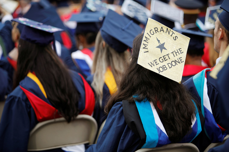 A graduate wears a mortar board adorned with a message in support of immigrants before the start of commencement exercises at Liberty University in Lynchburg, Virginia