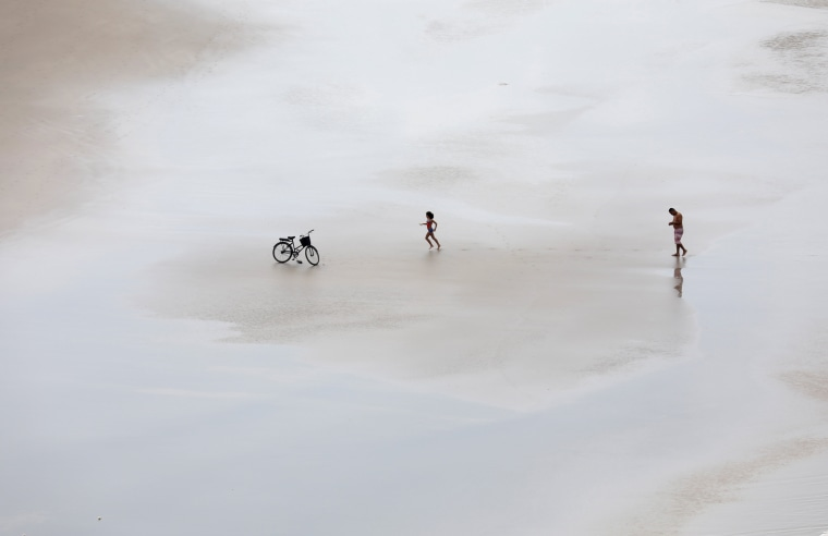 Image: A girl runs towards her bicycle, accompanied by a relative, on a beach in Guaruja