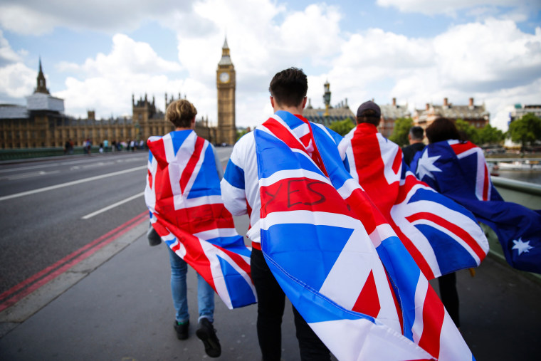 Image: People walk over Westminster Bridge wrapped in Union flags towards the Big Ben and The Houses of Parliament
