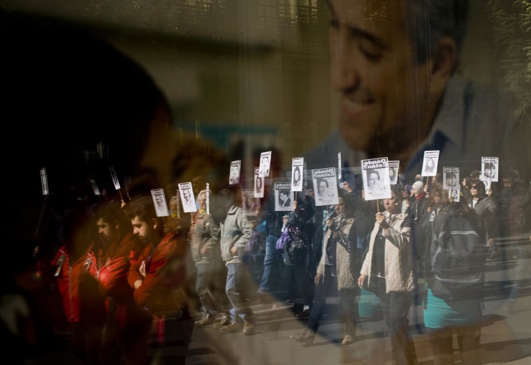 Image: Protesters whose family members or friends were detained and never heard from again during the Pinochet dictatorship are reflected in an office window advertising private pension plans, in Santiago, Chile
