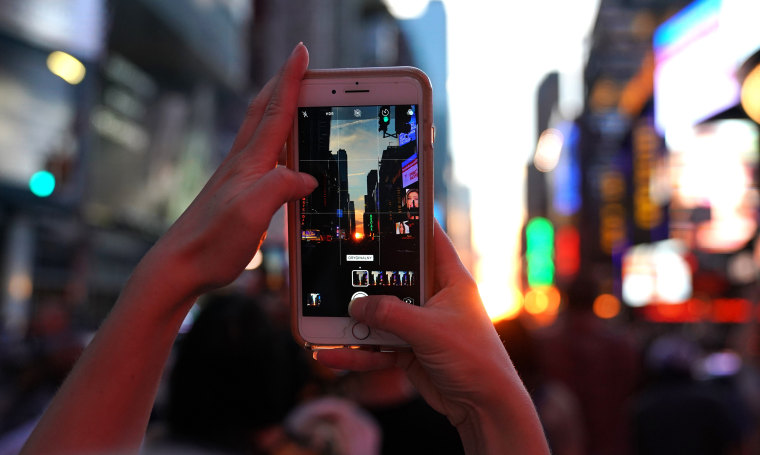 A woman takes a photo with her mobile phone as the sun sets in New York City on July 12, 2018.