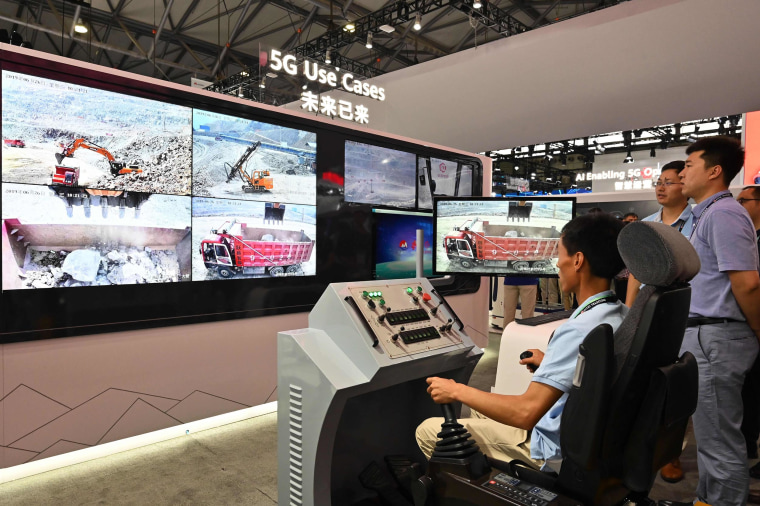 Image: A man tries out a remote control machine with 5G technology at a Huawei stand during the Mobile World Congress introducing next-generation technology at the Shanghai New International Expo Center