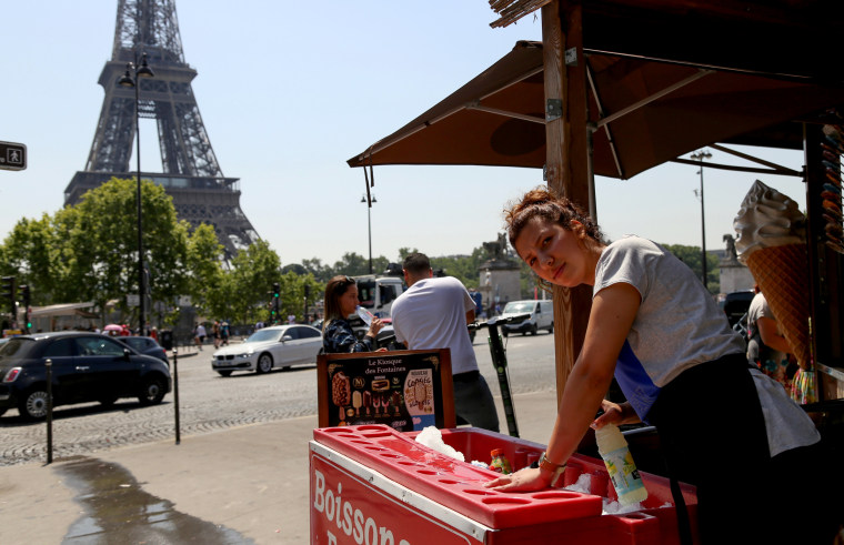 Image: Chaima Boutouil, 25, sells drinks and ice cream in view of the Eiffel Tower amid a heat wave in Paris.