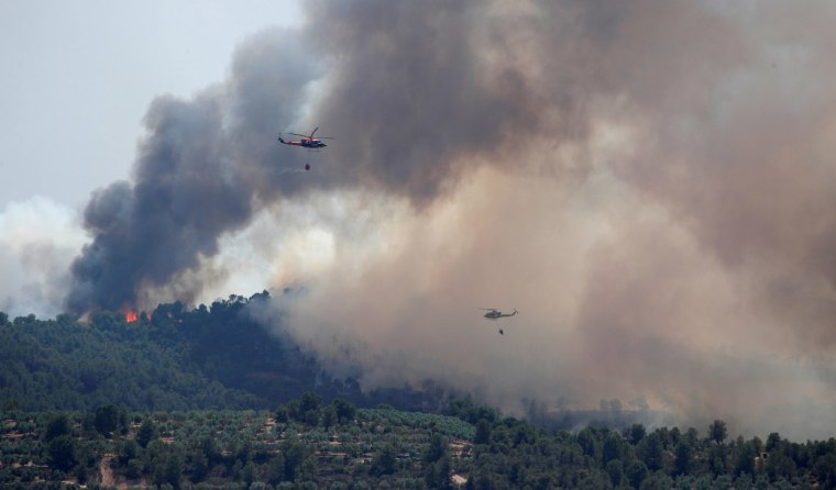 Image: Helicopters drop water over a forest fire during a heatwave near Bovera, west of Tarragona, Spain