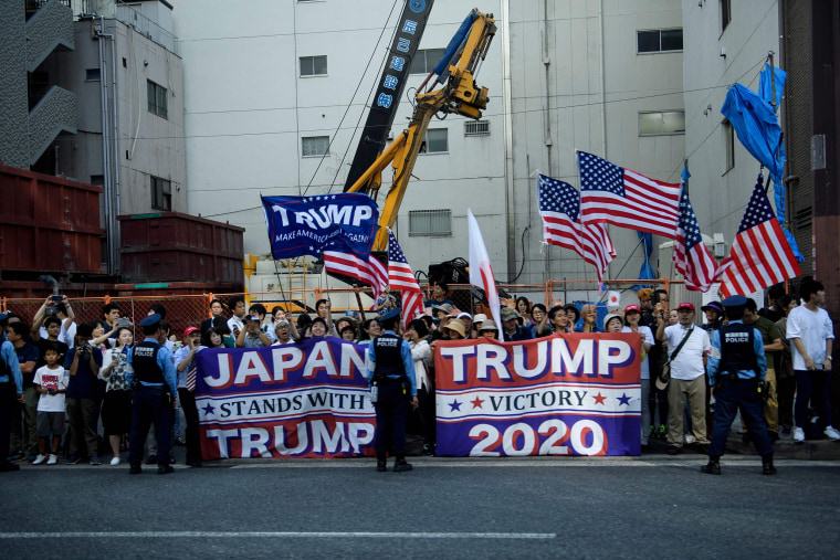 Image: People watch the motorcade with President Donald Trump drive by during the G20 Summit in Osaka