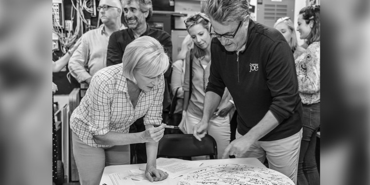 """Mika Brzezinski and Joe Scarborough sign their names at an """"Earn It!""""event at Books & Books in Coral Gables, Florida."""