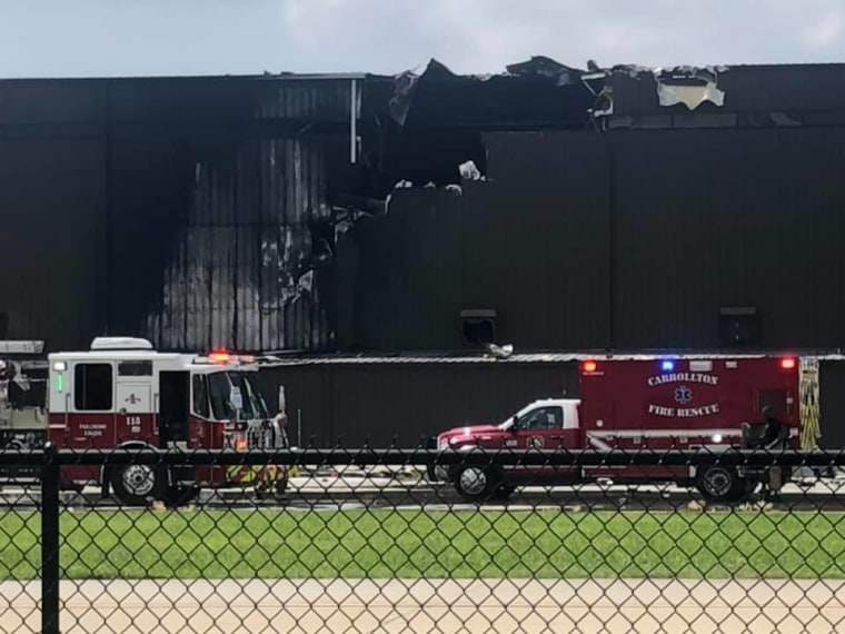 First responders attend to the scene of the crash, a charred hangar at Addison Airport.