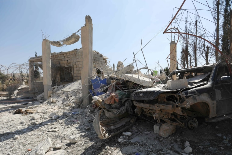 Image: The ruins of a building and the wreckage of a vehicle in Syria's northwestern Aleppo province