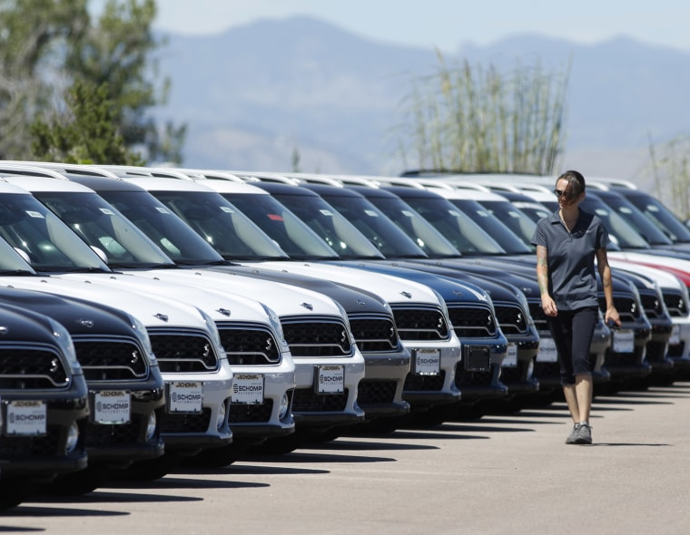 A lot technician passes by a long line of unsold cars at a dealership in Highlands Ranch