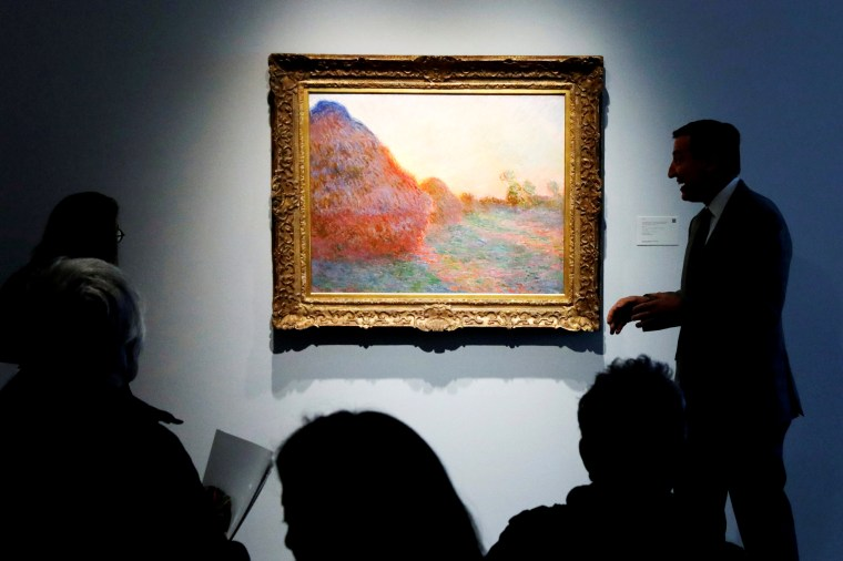 """Image: A painting by Claude Monet, part of the Haystacks """"Les Meules"""" series, at Sotheby's during a press preview for an art sale in New York on May 3, 2019."""