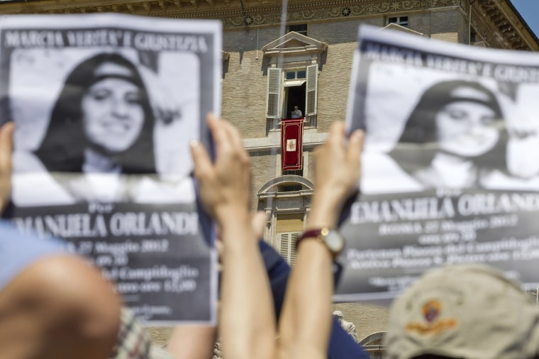 Image: Demonstrators hold pictures of Emanuela Orlandi, as Pope Benedict XVI, background center, reads his message during the Regina Coeli noon prayer in St. Peter's square, at the Vatican