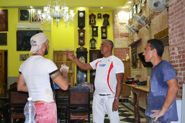 "David Diaz, owner of Havana bed and breakfast ""Casa David y Lidia Diaz,"" meets with carpenters who specialize in restoring colonial homes."