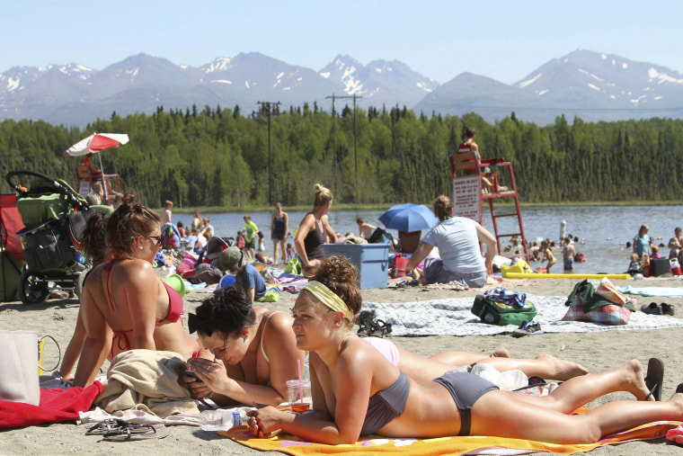 People sunbathe at Goose Lake in Anchorage, Alaska, as a heat wave hit the state on June 17, 2013.