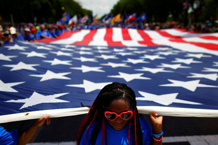Image: A girl carries a U.S. flag as she takes part in a parade during Fourth of July Independence Day celebrations in Washington, D.C.
