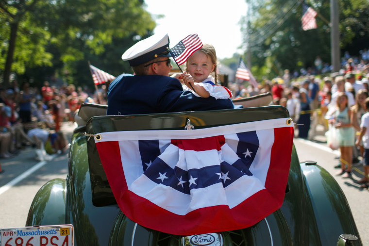 Image: A man and a girl ride in an antique Ford automobile during the annual 4th of July parade in Barnstable Village on Cape Cod, Massachusetts