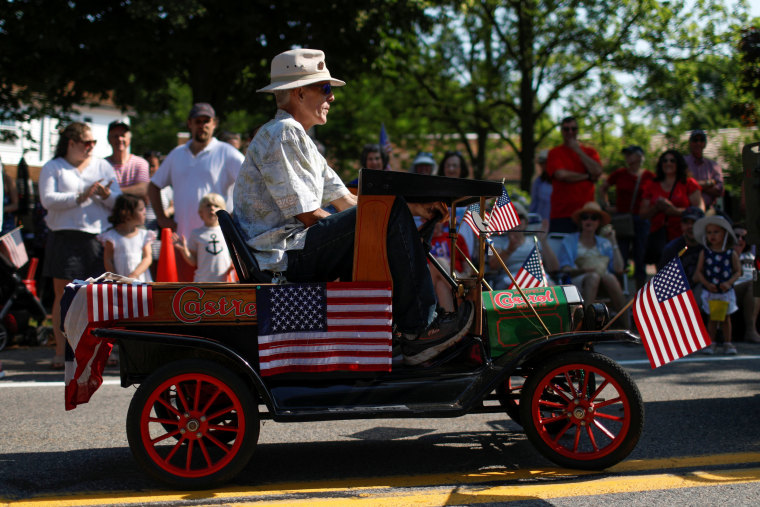 Image: A man rides in a miniature a car during the annual 4th of July parade in Barnstable Village on Cape Cod, Massachusetts