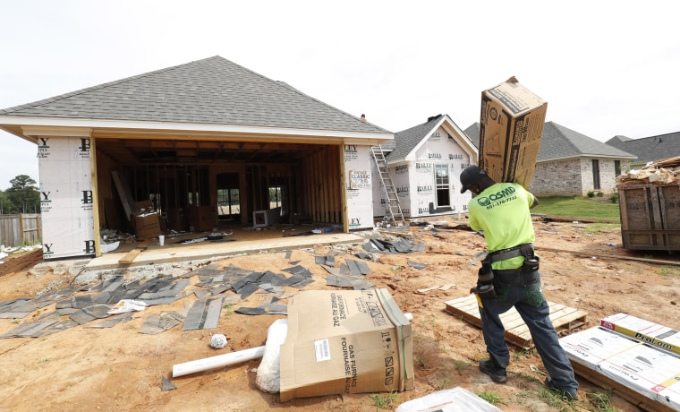 A worker carries supplies for a new house in Brandon, Mississippi, on June 19, 2019.