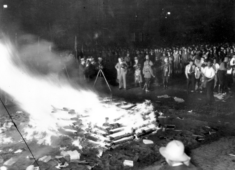 """A crowd gathers to witness thousands of books, considered to be """"un-German,"""" burn in Opera Square in Berlin during the Buecherverbrennung book burnings on May 10, 1933."""