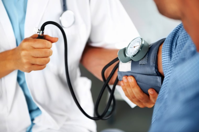 A doctor listening to his patient's heartbeat with a stethoscope