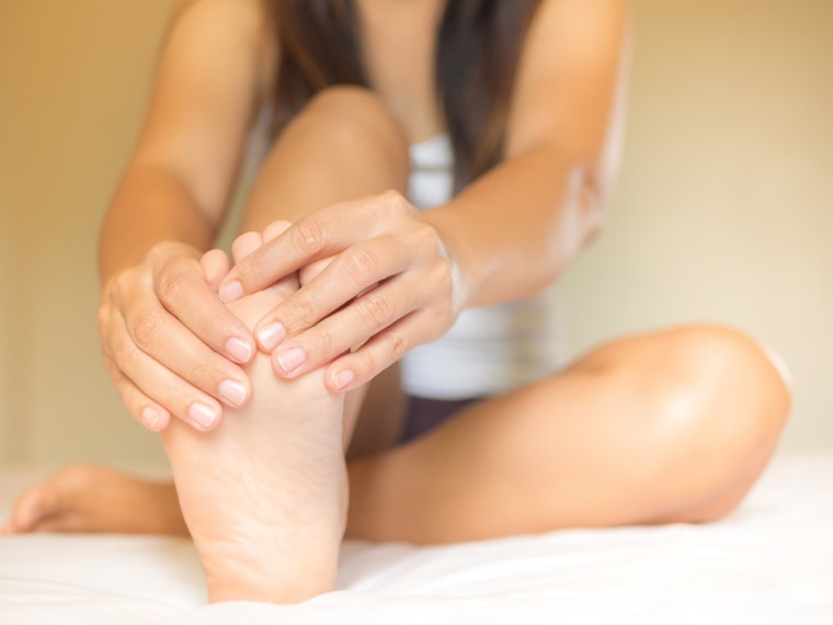 Image: Low Section Of Woman Touching Foot In Pain While Relaxing On Bed