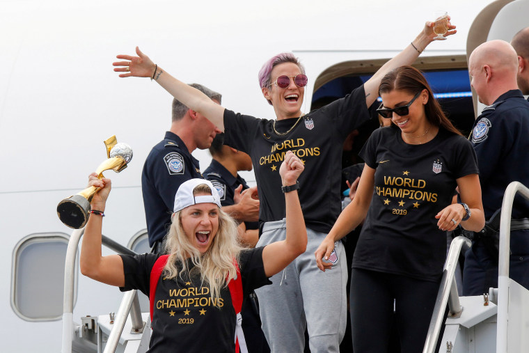 Image: U.S. soccer players Julie Ertz, Megan Rapinoe and Alex Morgan celebrate as they exit the plane with the Trophy for the FIFA Women's World Cup after they arrive at the Newark International Airport