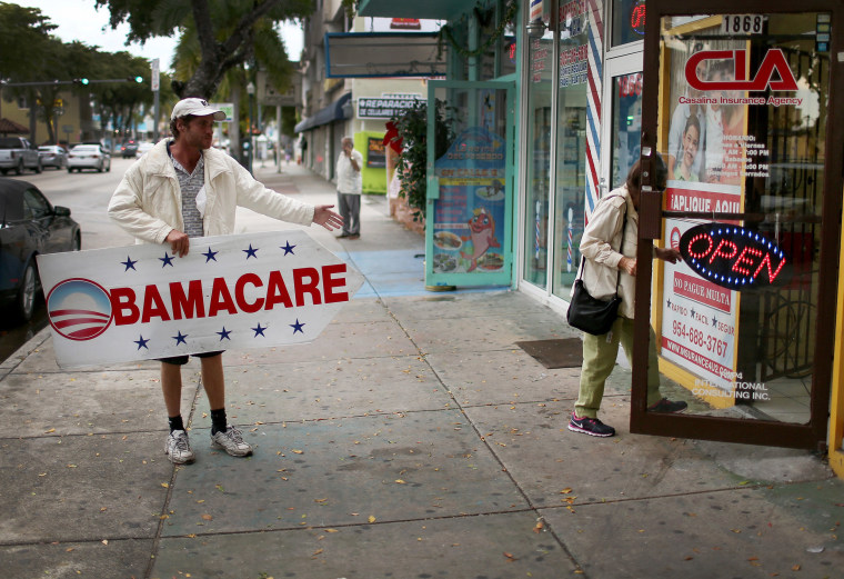 Image: Pedro Rojas holds a sign directing people to an insurance company where they can sign up for the Affordable Care Act, also known as Obamacare in Miami, Florida.