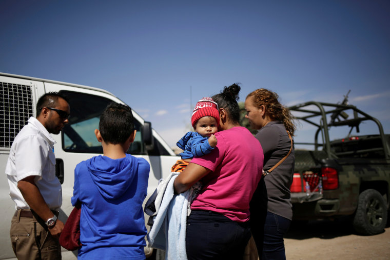 Image: An agent of the National Migration Institute (INM) talks to Honduran migrants after being stopped from crossing the border into the United States by members of the Mexican National Guard, in Ciudad Juarez