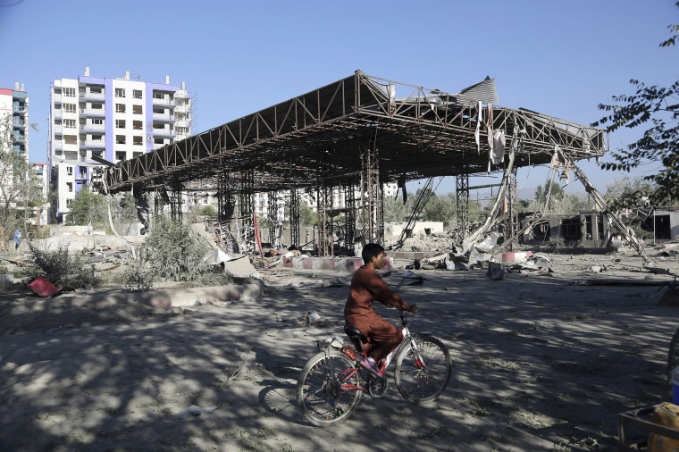 Image: An Afghan boy rides a bicycle through the aftermath of an attack in Kabul, Afghanistan