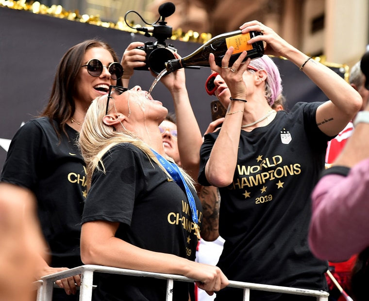 Image: Megan Rapinoe pours champagne for Ali Krieger during the ticker-tape parade in New York on July 10, 2019.