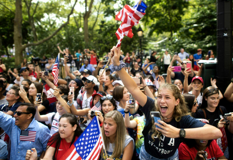 """Image: Fans cheer as the parade continues up the Canyon of Heroes. Several players led the crowds in chants of \""""Equal Pay\"""""""