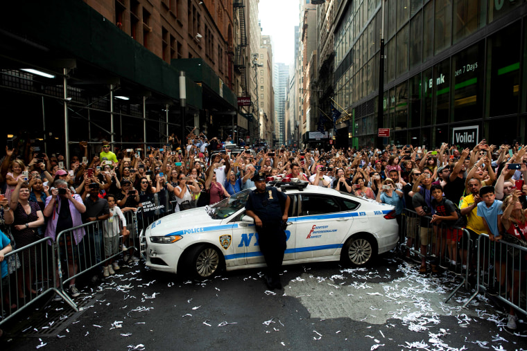 Image: A police officer watches as crowds cheer during the ticker-tape parade celebrating the U.S. women's soccer team World Cup victory in New York on July 10, 2019.