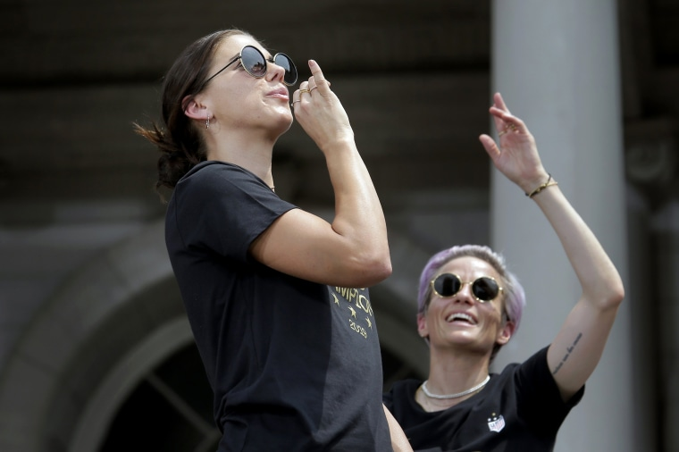 """Image: Alex Morgan \""""sips tea,\"""" a nod to her infamous goal celebration against England, at City Hall on July 10, 2019."""