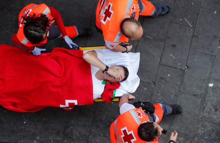Image: A reveller is helped by medical staff during the running of the bulls at the San Fermin festival in Pamplona, Spain,