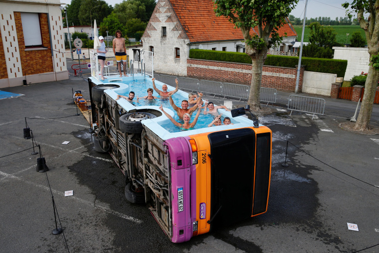 """Image: People bathe in a decommissioned city bus named \""""le bus piscine\"""", an artwork by the French artist Benedetto Bufalino in Gosnay near Bethune"""
