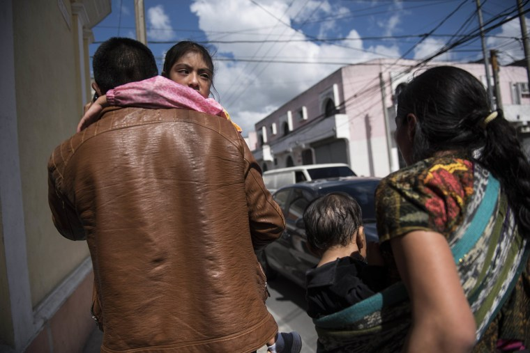 "Image: Seven-year-old Mayra Cristina Gregorio Velasquez is carried by her father after they were reunited at the shelter ""Nuestras Raices,"" following her detention by U.S. immigration authorities, in Guatemala City"