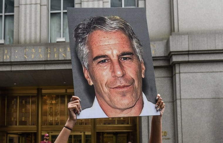 Image: A protester holds up a placard with a photo of Jeffrey Epstein in front of the federal courthouse