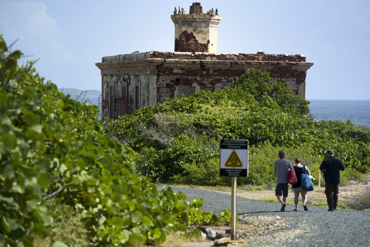 Tourists walk toward Ferro Port lighthouse, at Verdiales Key point on the south coast of Vieques island, Puerto Rico on Jan. 13, 2017. The tiny island long known for a former Navy bombing range is gradually working toward a different sort of boom: a growing tourist mecca.