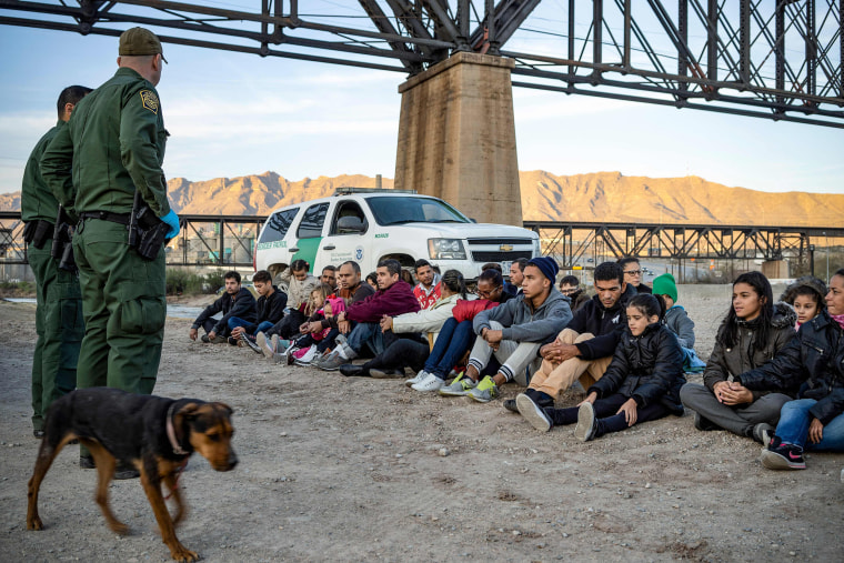 Image: A group of about 30 Brazilian migrants, who had just crossed the border, sit on the ground near US Border Patrol agents, on the property of Jeff Allen, who used to run a brick factory near Mt. Christo Rey on the US-Mexico border in Sunland Park, Ne