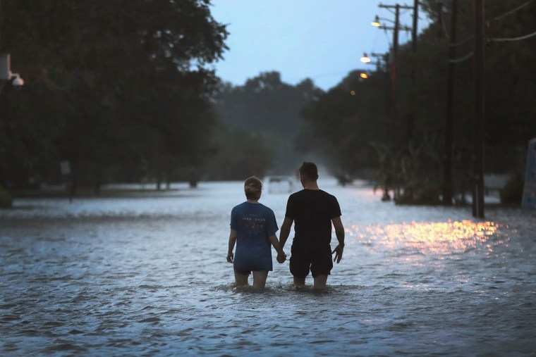 Image: A couple stroll down Lakeshore Drive along the shore of Lake Pontchartrain after it was flooded in the wake of Hurricane Barry on July 13, 2019 in Mandeville, Louisiana.