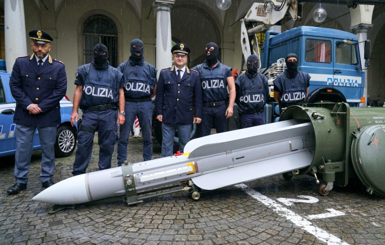 Image: Police stand with a missile seized at an airport hangar near Pavia after an investigation into Italians who took part in a Russian-back insurgency in the Ukraine on July 15, 2019.