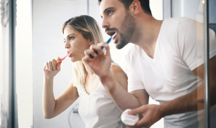 Image: Couple brushing teeth in the morning.