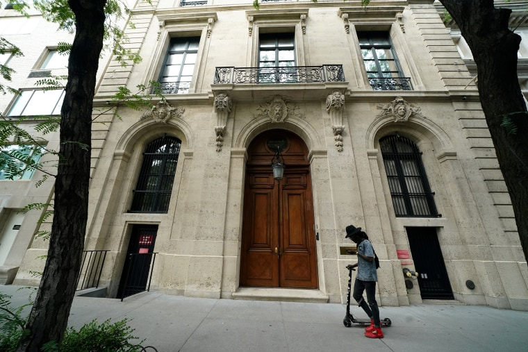 Image: A man walks past the front door of the upper east side home of Jeffrey Epstein in New York