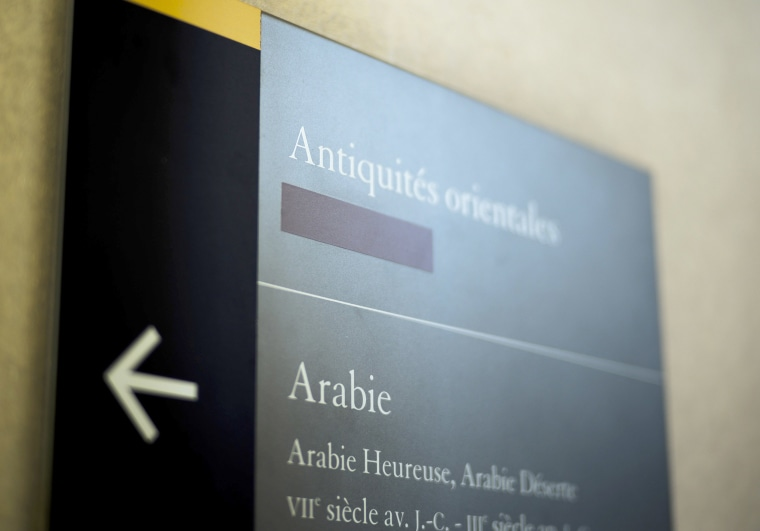 Image: A taped over sign is pictured at the Louvre Museum in Paris, France