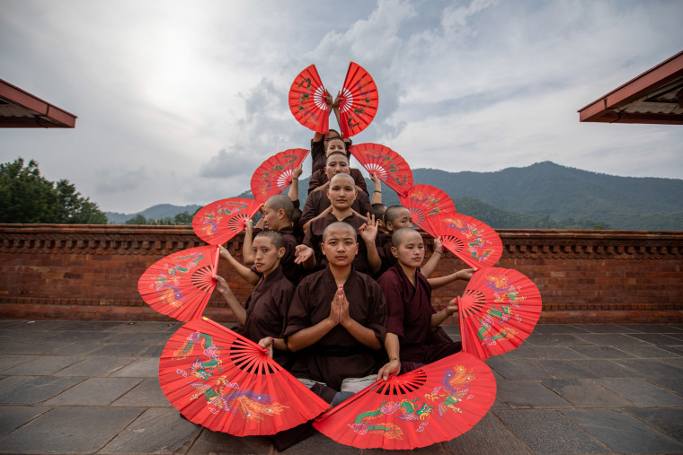 The Kung Fu Nuns of Drukpa Order strike a traditional pose with their fans during a training session at the Druk Gawa Khilwa Nunnery in Kathmandu.  This is the home to hundreds of 14 to 30-year-old nuns, rewriting their place in the Buddhist hierarchy, while empowering girls from villages across the Himalayas - through Kung Fu.