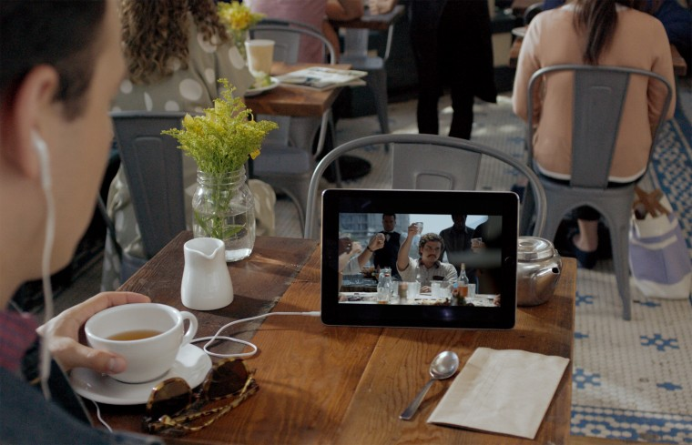 A man watches Netflix on a device in a restaurant