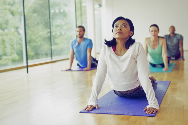 Woman in upward facing dog position in yoga class