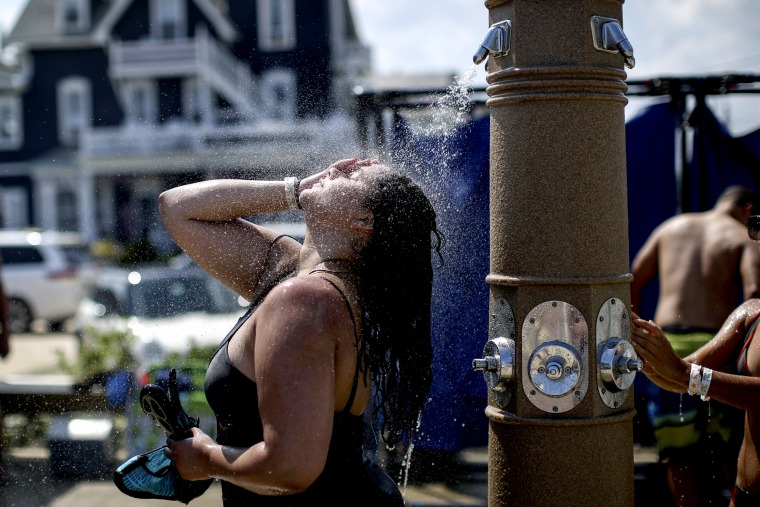 Image: A woman washes off on the beach in Ocean Grove, New Jersey, on July 20, 2019. Many areas of the United States were under excessive heat watches as temperatures soared to record levels.