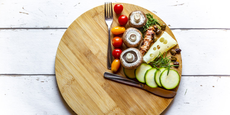 Vegetables on round chopping board, symbol for intermittent fasting