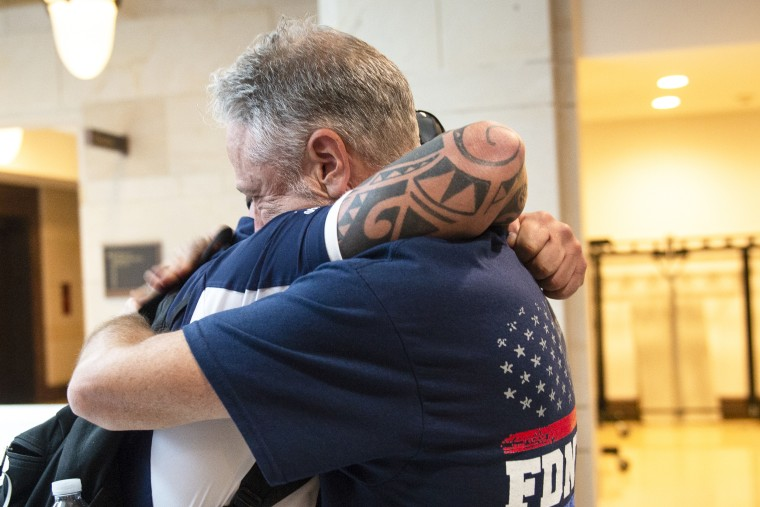 John Feal, 9/11 first responder, left, and Jon Stewart, former host of The Daily Show, hug after the Senate passed a bill for the permanent authorization of September 11th Victim Compensation Fund on Capitol Hill in Washington on Tuesday July 23, 2019.